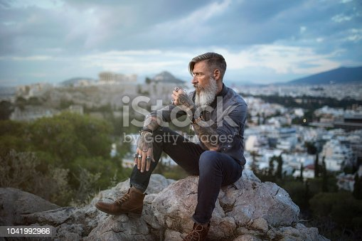 istock Attractive hipster with a beard is sitting on a rock high over Athens City with Acropolis view 1041992966