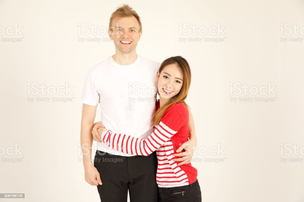 Attractive inter racial couple being close together stock photo