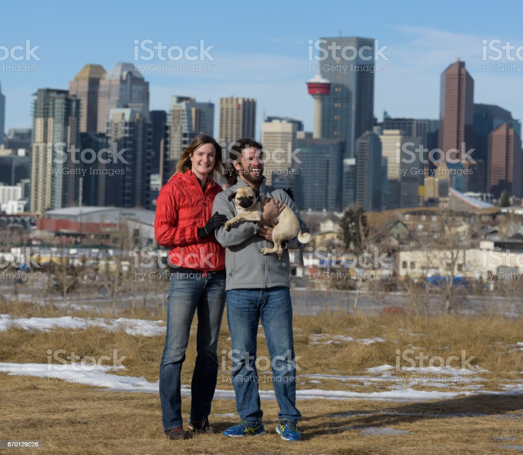 Attractive Interracial Couple Having Fun On a Cool Day with Healthy Pug stock photo