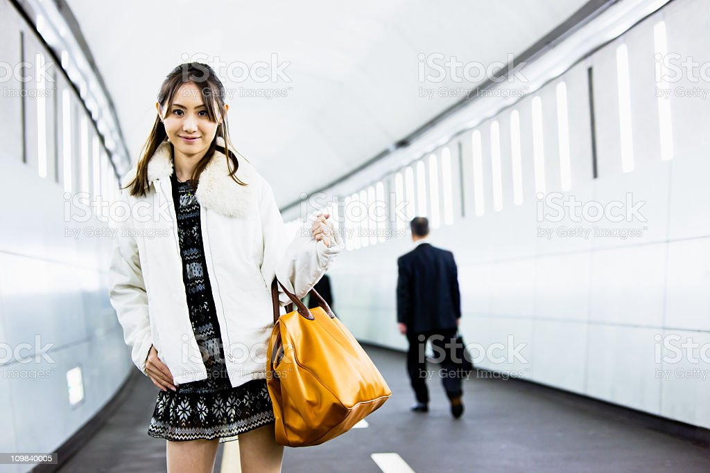 Attractive Japanese Woman Subway Corridor Attractive japanese woman with leather shopping bag standing in the neo light of tokyo subway station tunnel. 20-29 Years Stock Photo