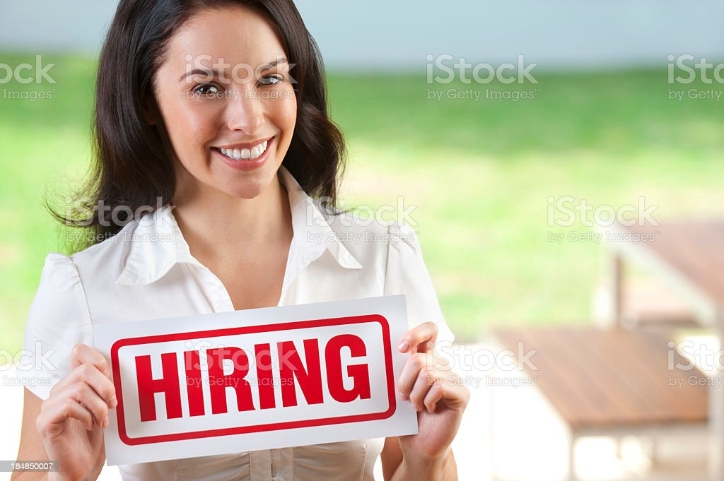 Attractive job woman holding hiring sign royalty-free stock photo