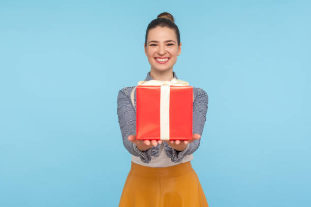Attractive joyful fashionably dressed woman with hair bun giving gift box and smiling broadly, holding out present to camera stock photo