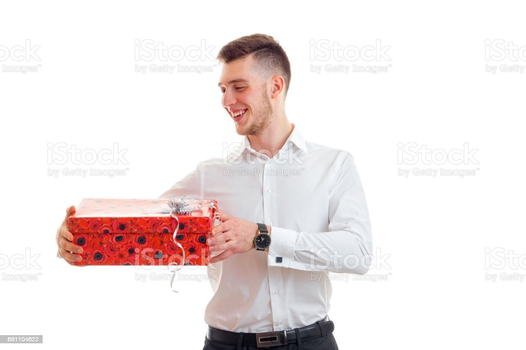 attractive joyful young man holding a large gift packaging stock photo