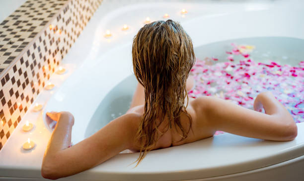 Attractive lady lying in bath with rose petals stock photo