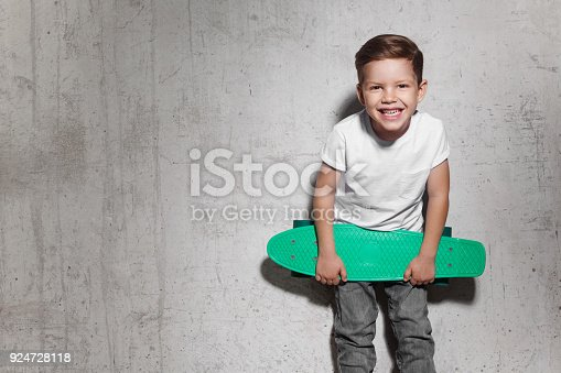 istock Attractive little boy with green skateboard in his hands 924728118