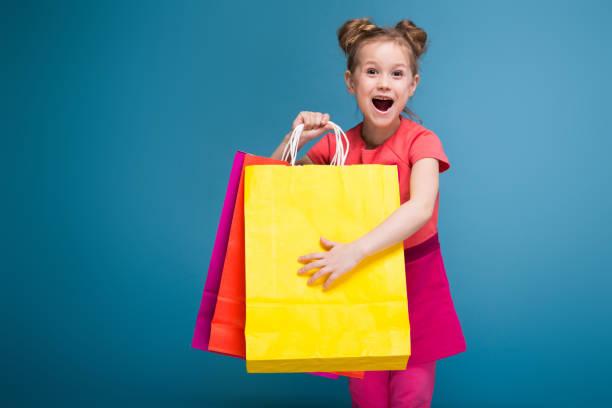attractive little cute girl in pink dress holds purple paper bag - taschen von liebeskind stock-fotos und bilder