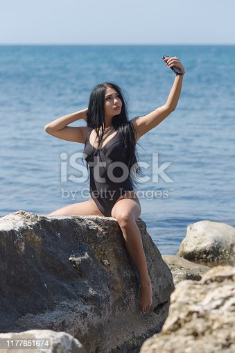 Attractive long haired brunette person resting at secluded place of wild rocky seashore. Dark haired young woman in black one-piece swimsuit takes selfie against sea