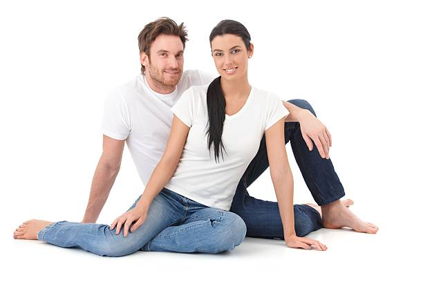 Attractive loving couple sitting on floor smiling stock photo