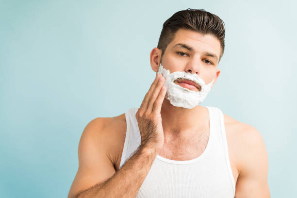 attractive male applying foam against plain background - shaving cream stock pictures, royalty-free photos & images
