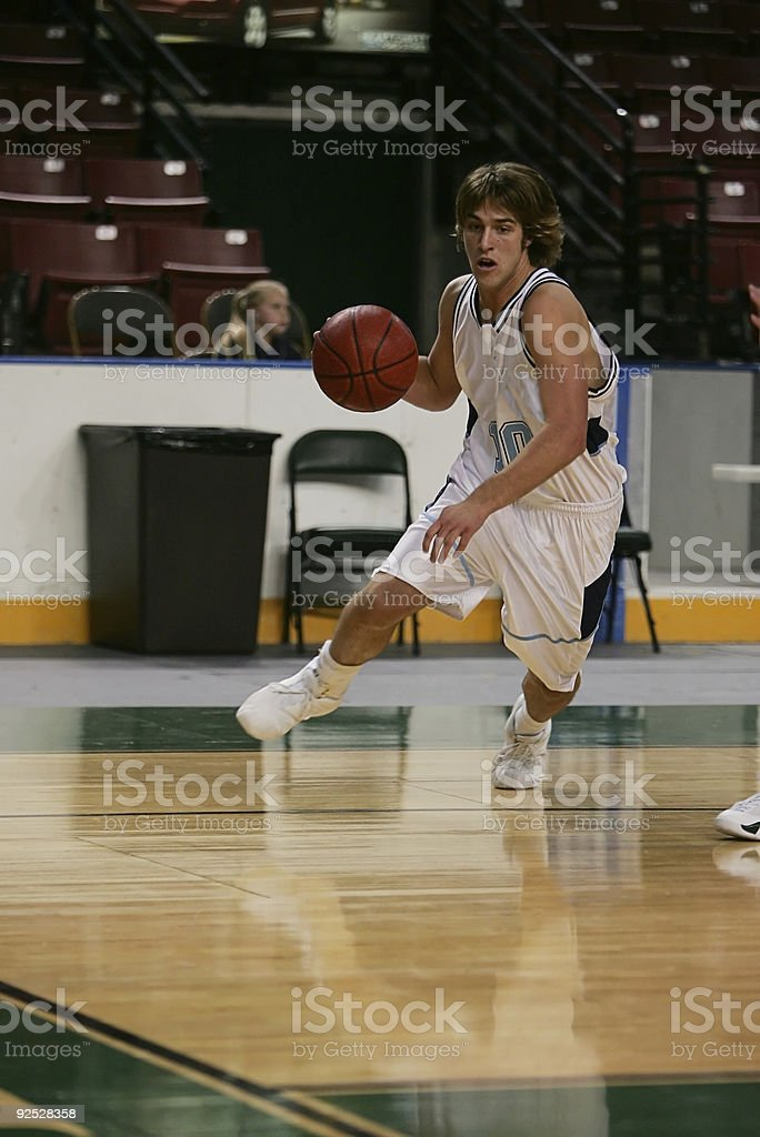 Attractive Male Basketball Player Dribble Drives Toward Baseline stock photo
