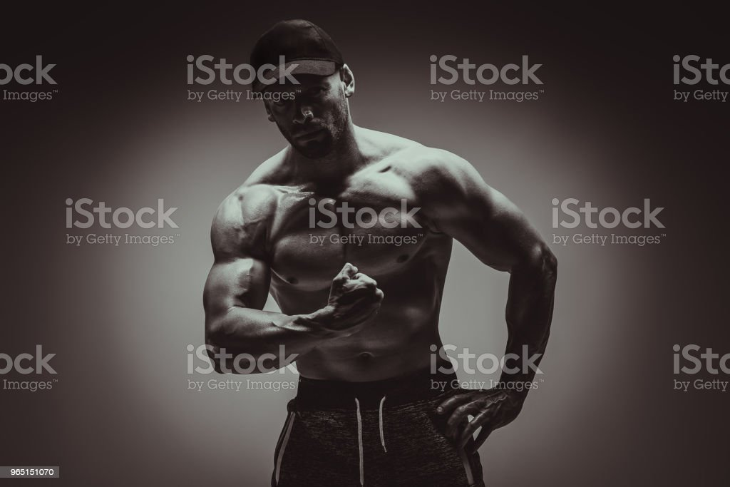 Attractive male body builder flexing his biceps muscles in studio shot. Concept Gym Life Style. royalty-free stock photo
