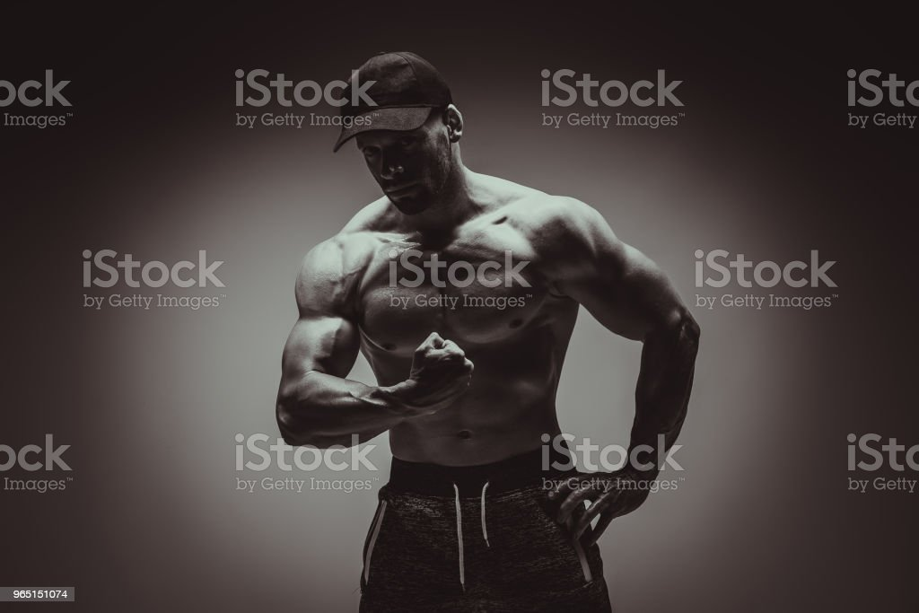 Attractive male body builder flexing his biceps muscles in studio shot. Concept Gym Life Style. zbiór zdjęć royalty-free