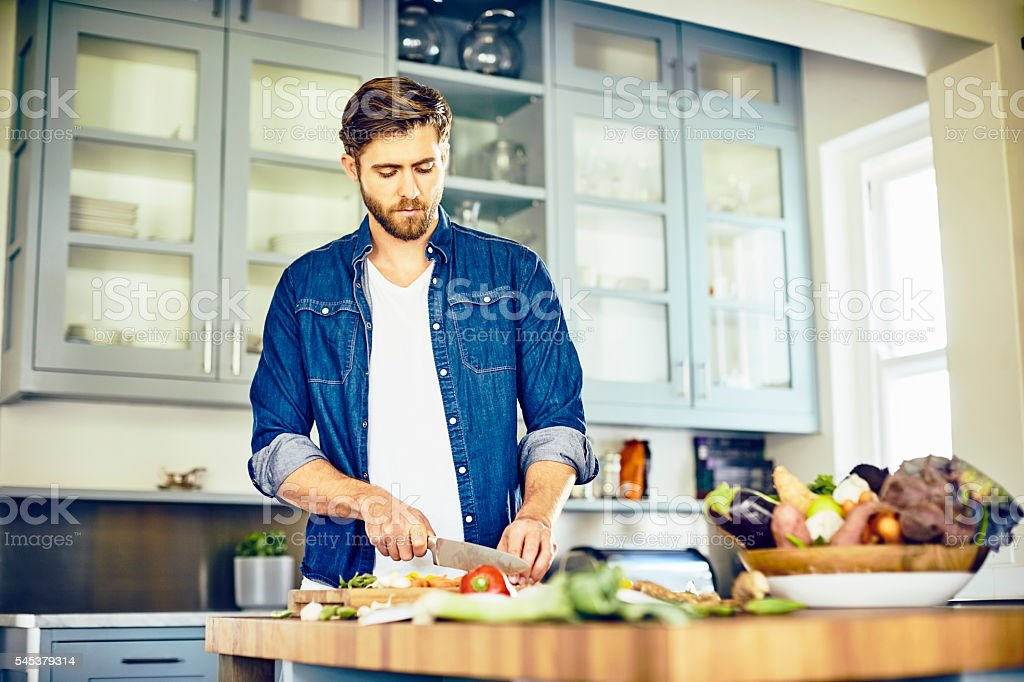 Attractive male cutting vegetables at kitchen island – Foto
