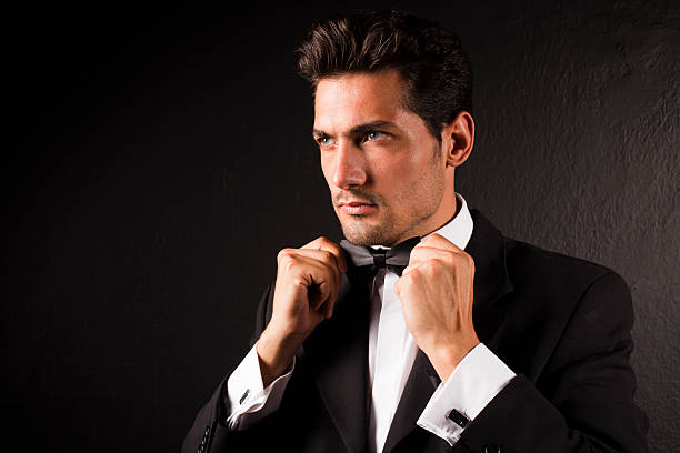 attractive male model tying bow tie - tuxedo stock photos and pictures