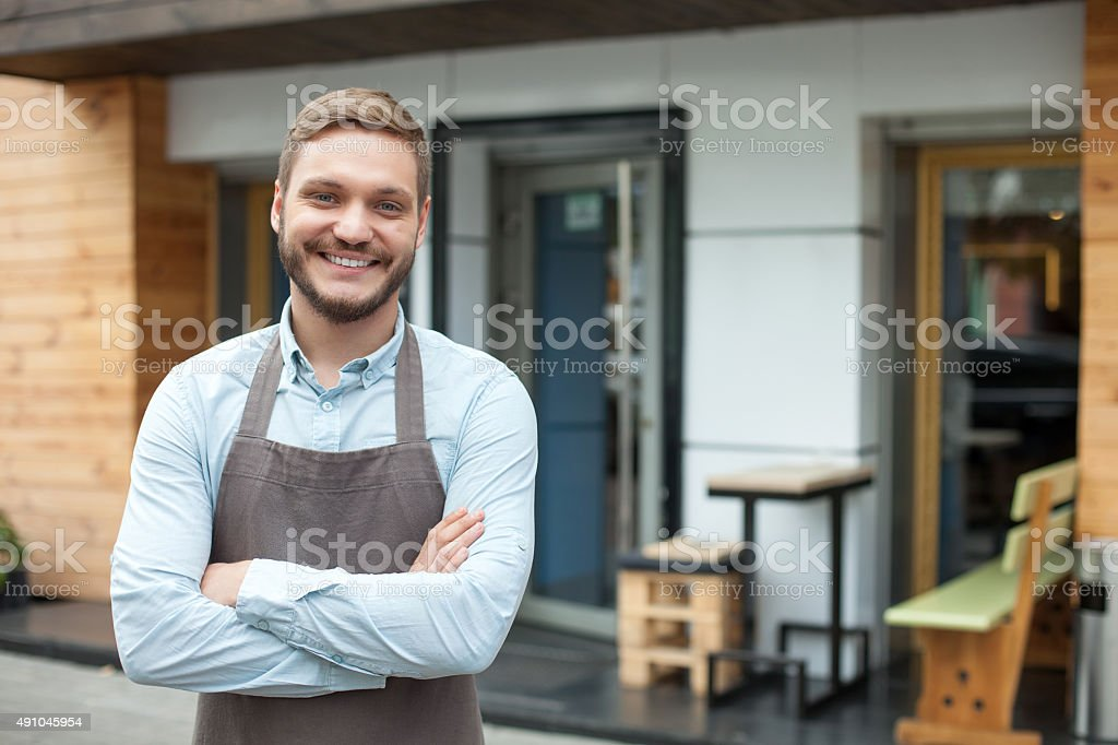 Attractive male owner of cafeteria is waiting for customers stock photo