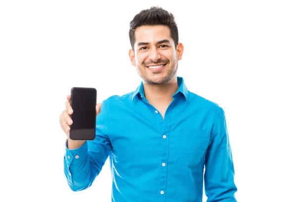 aantrekkelijke mannelijke glimlachen terwijl smartphone - tonen stockfoto's en -beelden