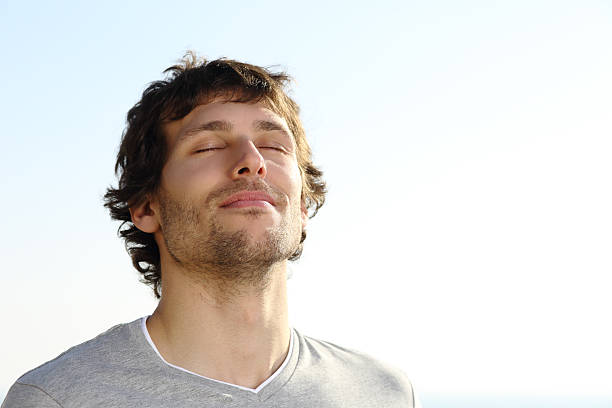 Attractive man breathing outdoor Attractive man breathing outdoor with the sky in the background tranquil scene stock pictures, royalty-free photos & images