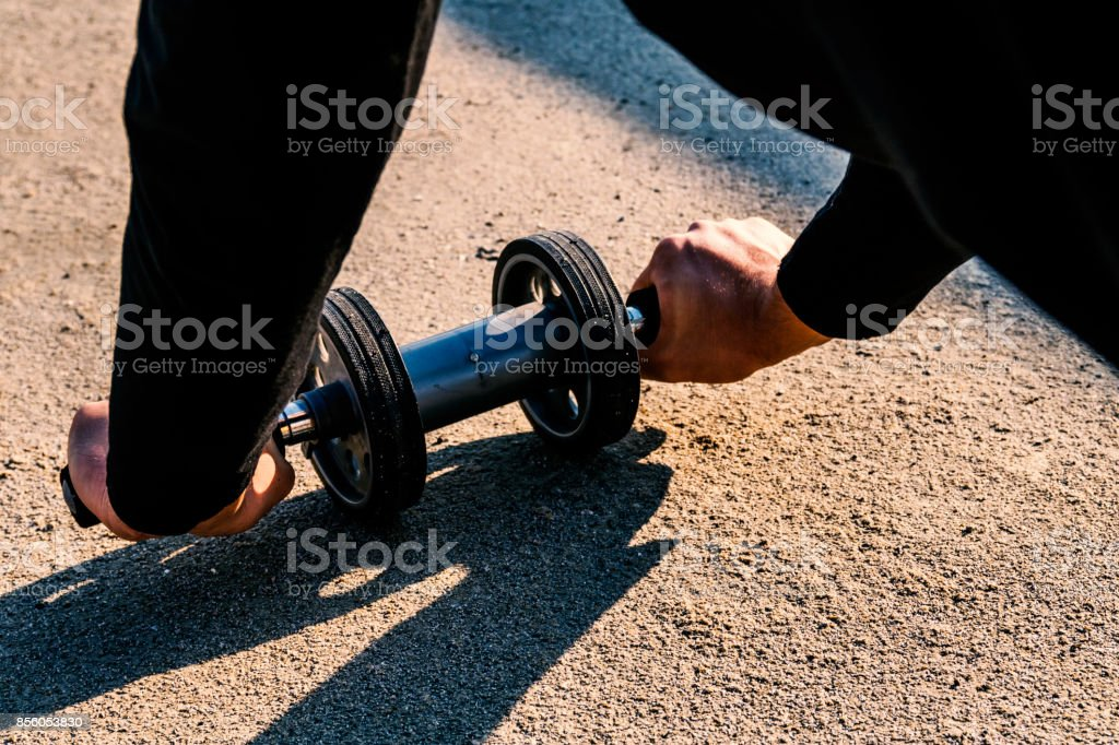 attractive man do abdominal exercises  with roller wheel stock photo