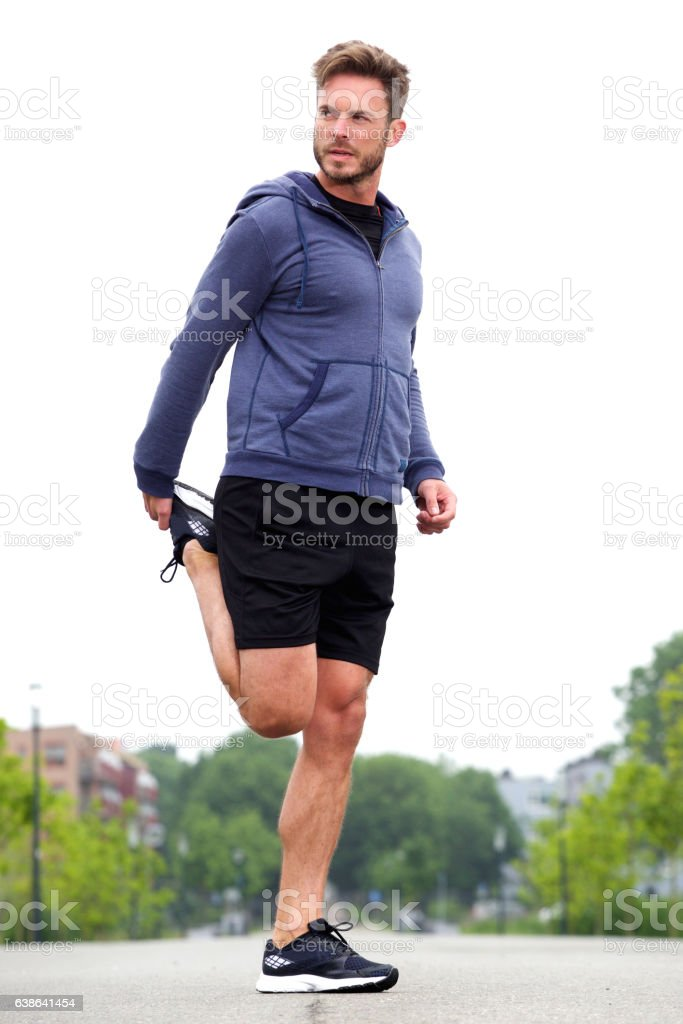 Attractive man doing stretch in street before run stock photo