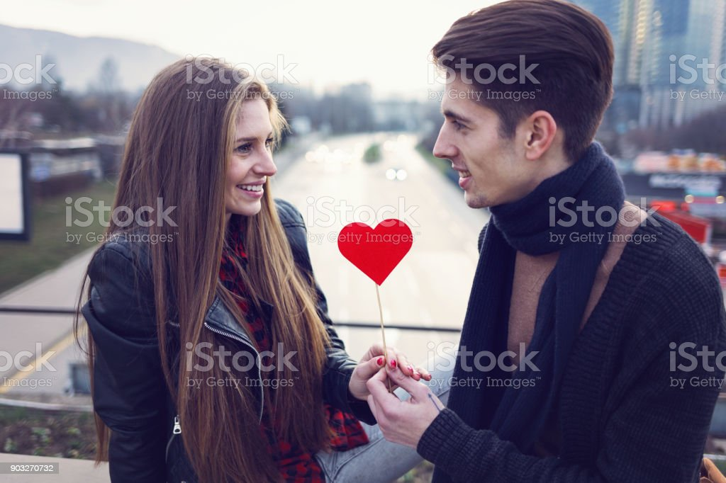 Attractive man giving red paper heart to his girlfriend stock photo