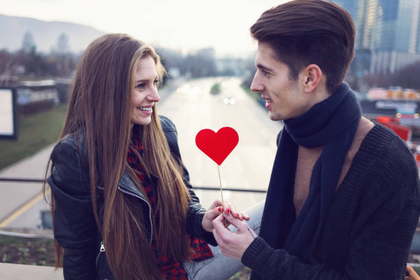 attractive man giving red paper heart to his girlfriend - i love you stock photos and pictures