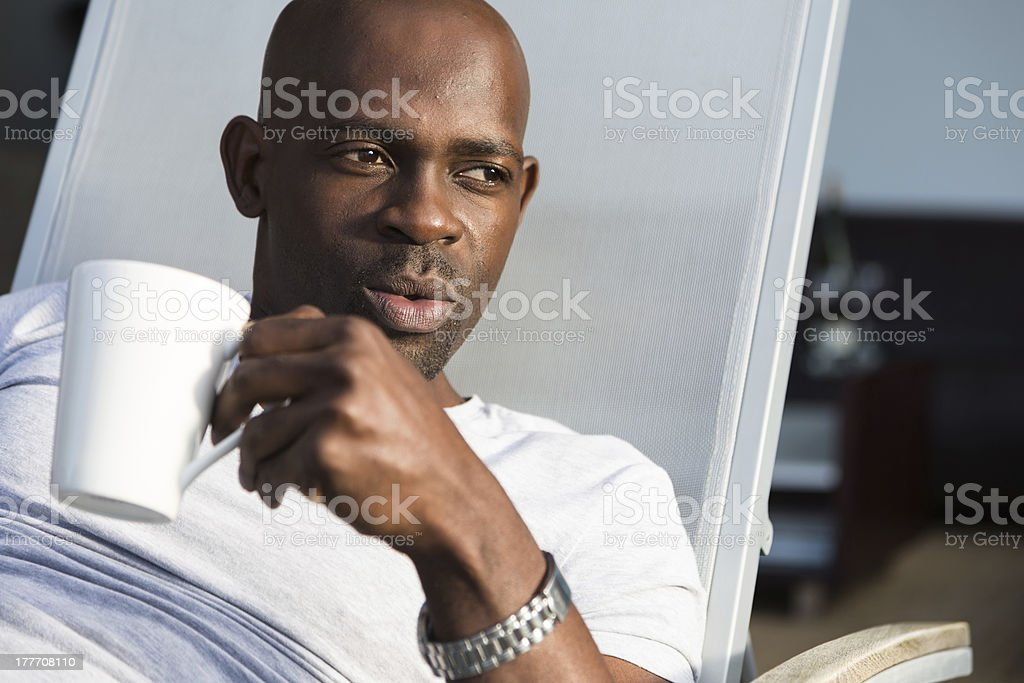Attractive Man Holding a Mug Looks to the Side stock photo