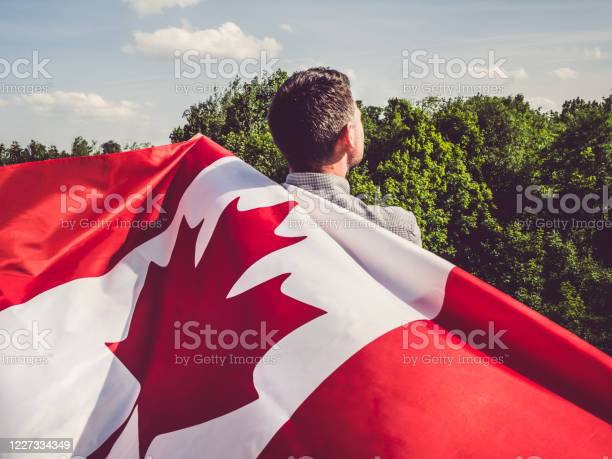 Photo of Attractive man holding Canadian Flag. National holiday
