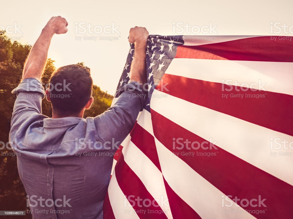 Attractive man holding waving in the wind US flag stock photo