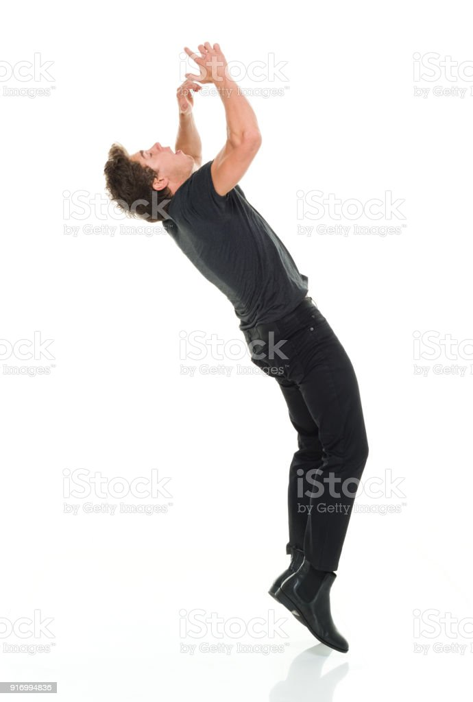 Attractive man in all black clothing doing back flips stock photo