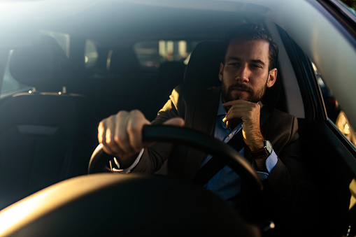 istock Attractive man in business suit driving car 1181579740