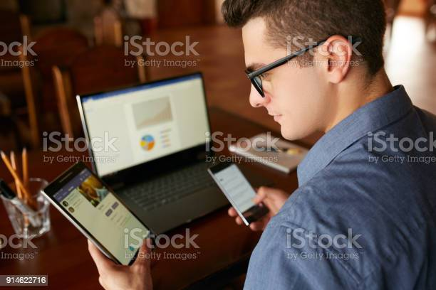 Attractive Man In Glasses Working With Multiple Electronic Internet Devices Freelancer Businessman Has Laptop And Smartphone In Hands And Laptop On Table With Charts On Screen Multitasking Theme Stock Photo - Download Image Now