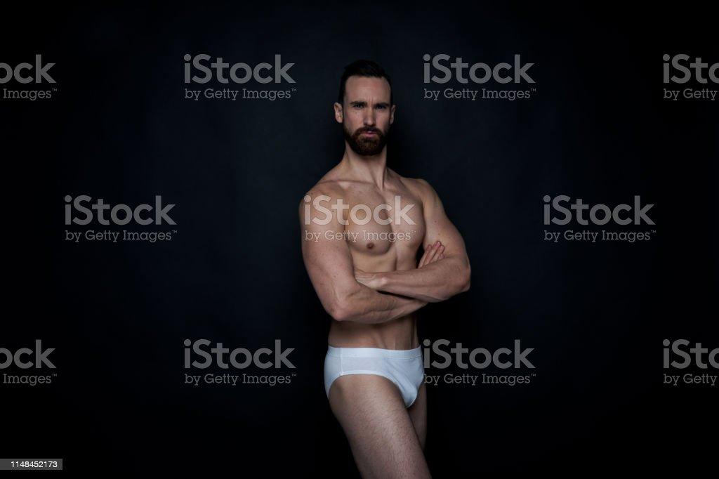 Attractive man in white underwear on black background