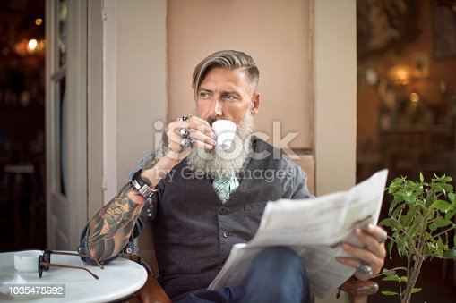 Attractive man is sitting in a coffee shop, drinking a coffee and reading the newspaper