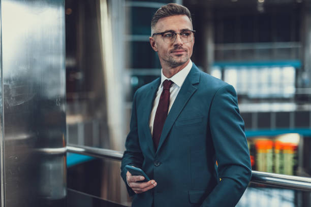 Attractive man looking aside with telephone in hand stock photo
