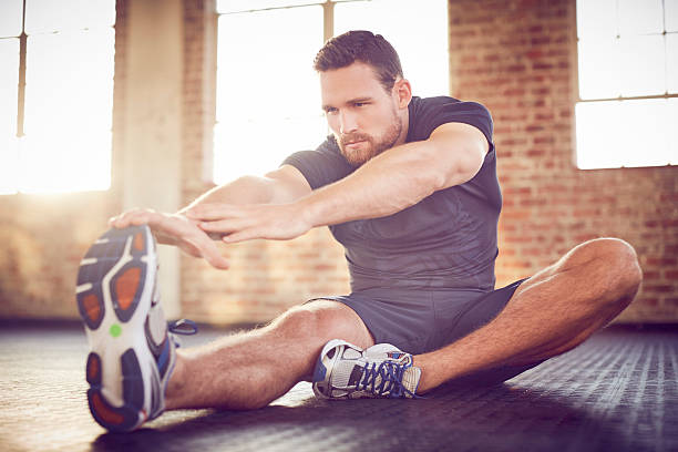 Attractive man performing stretching exercise in gym Attractive man performing stretching exercise in gym. Male is touching toe while sitting on floor. He is in health club. touching toes stock pictures, royalty-free photos & images