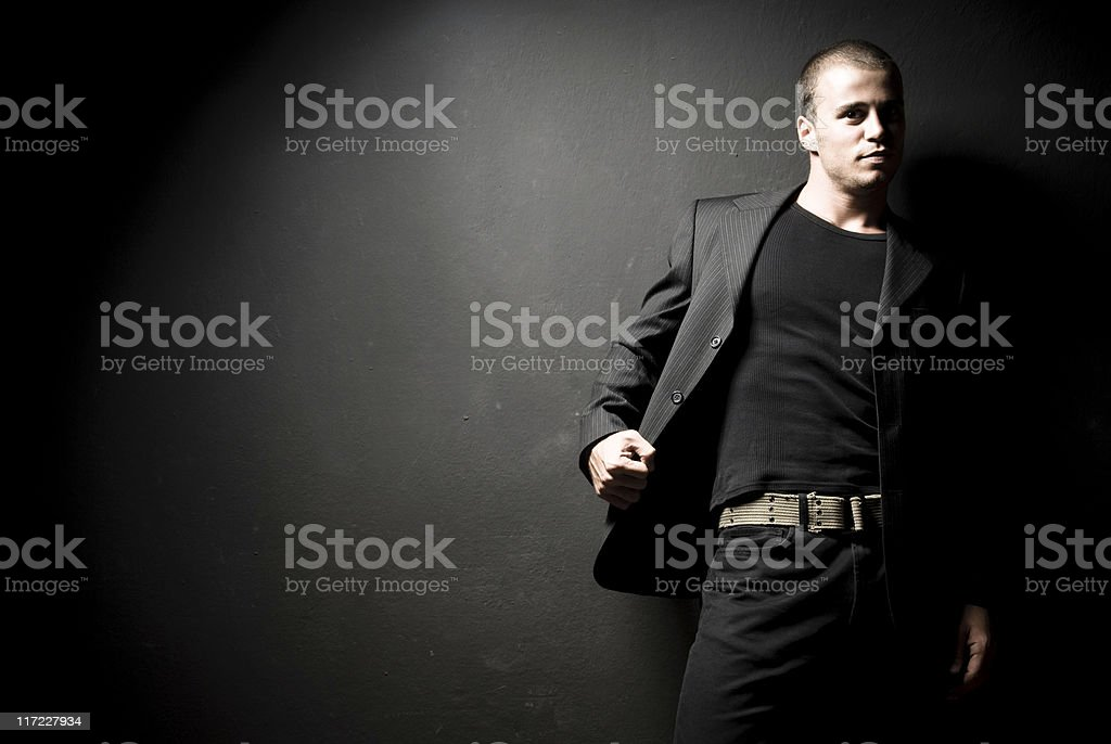 Attractive Man Young, attractive man in front of a black wall. 20-24 Years Stock Photo