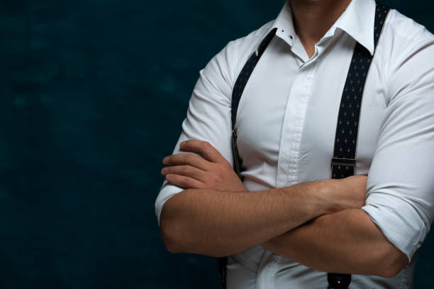 Attractive man posing on dark background Hands of an unidentified strong man in formal attire with suspenders folded on chest on blue grunge background suspenders stock pictures, royalty-free photos & images