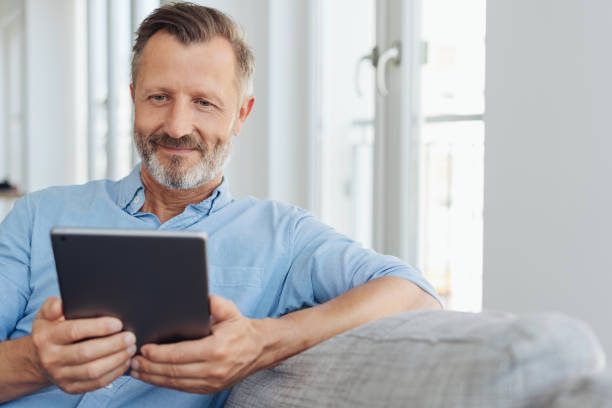 Attractive man relaxing on a sofa with a tablet-pc stock photo
