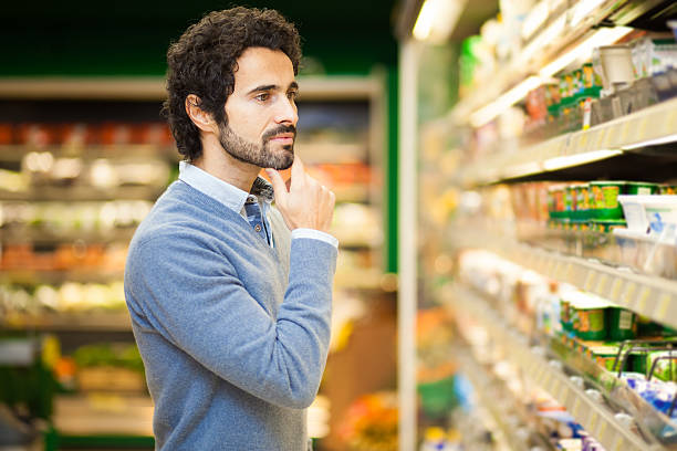 Attractive man shopping in a supermarket Attractive man shopping in a supermarket snack aisle stock pictures, royalty-free photos & images