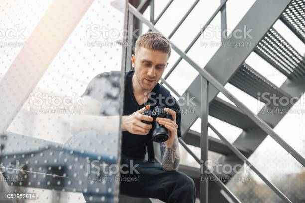 Attractive man sitting at staircase and checking photos in camera picture id1051952614?b=1&k=6&m=1051952614&s=612x612&h=4mbdwuivmt4zfixqgipndpnssjjrcecyx8n odpyb q=