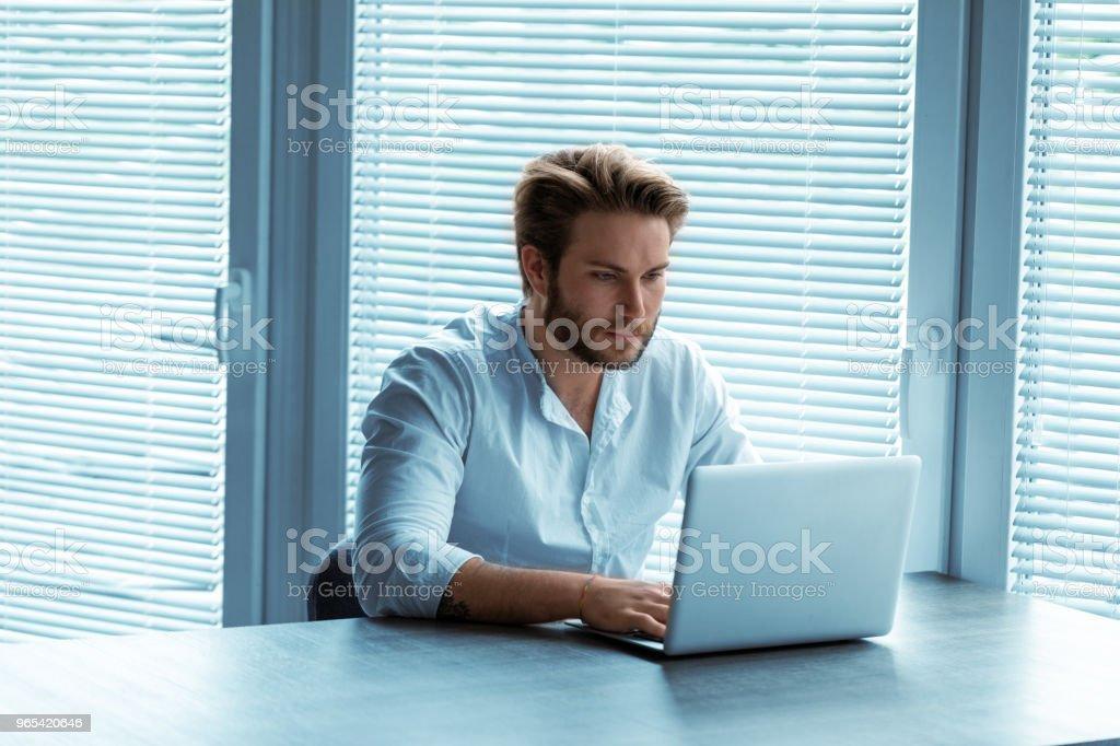 Homme séduisant assis à un ordinateur portable - Photo de Adulte libre de droits