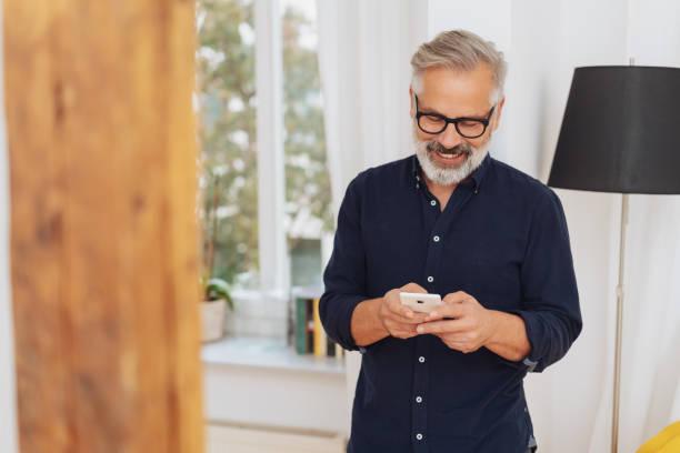 attraktiver mann lächelnd, als er eine sms-nachricht sendet - einzelner senior stock-fotos und bilder