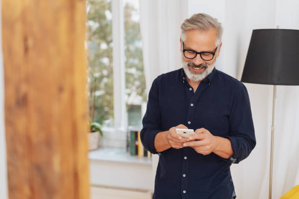 Attractive man smiling as he sends a text message Attractive man smiling as he sends a text message on his mobile phone while standing indoors at home only senior men stock pictures, royalty-free photos & images