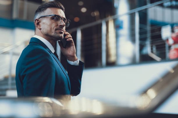 Attractive man speaking on telephone with boss stock photo