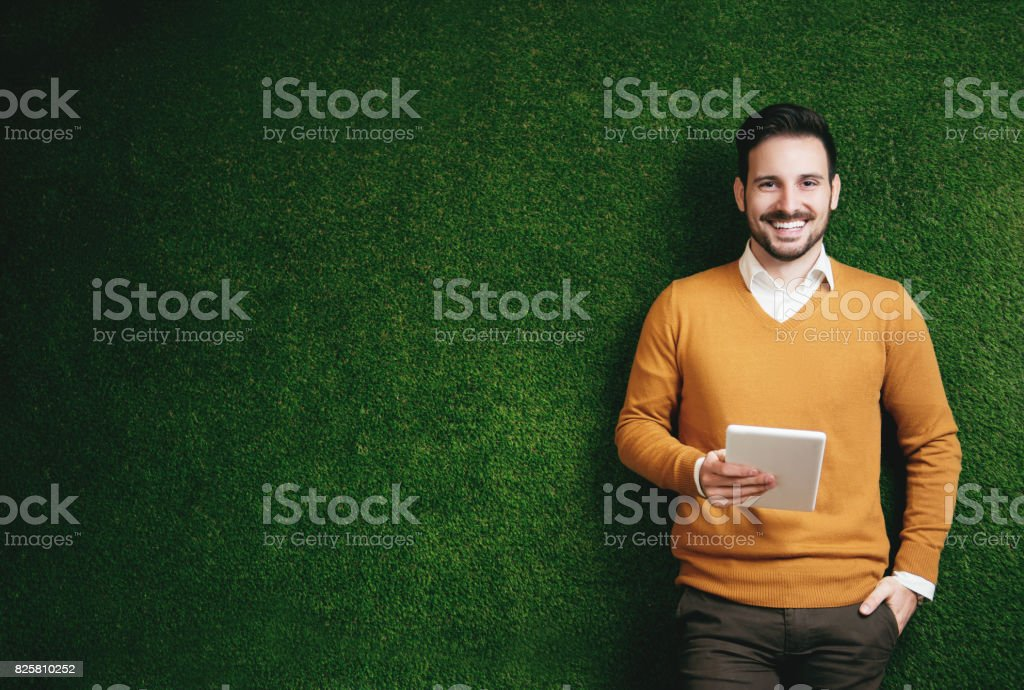 Attractive man standing over a green grass wall, holding a tablet stock photo