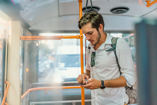 Attractive man talking on the phone in public bus