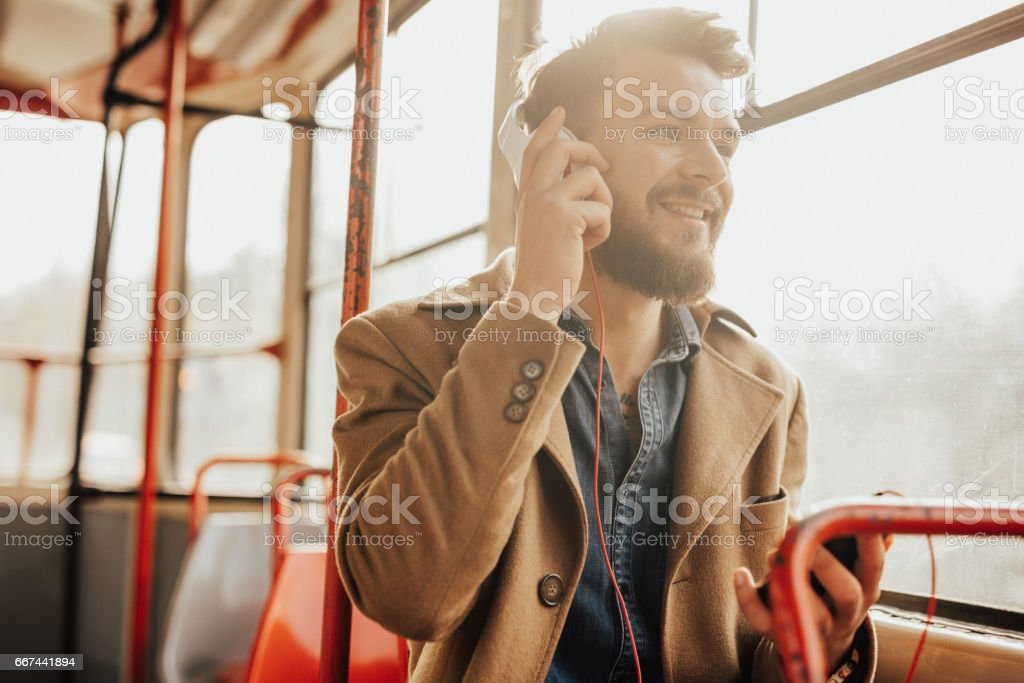 Attractive man talking on the phone in public bus stock photo