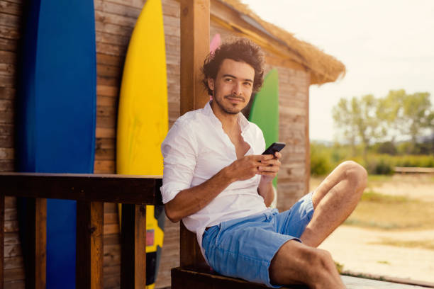 Attractive man texting at a beach bar stock photo