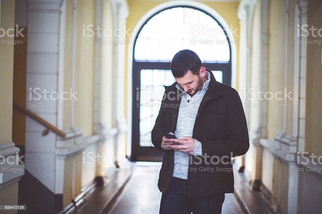 Attractive man typing on his smart phone stock photo