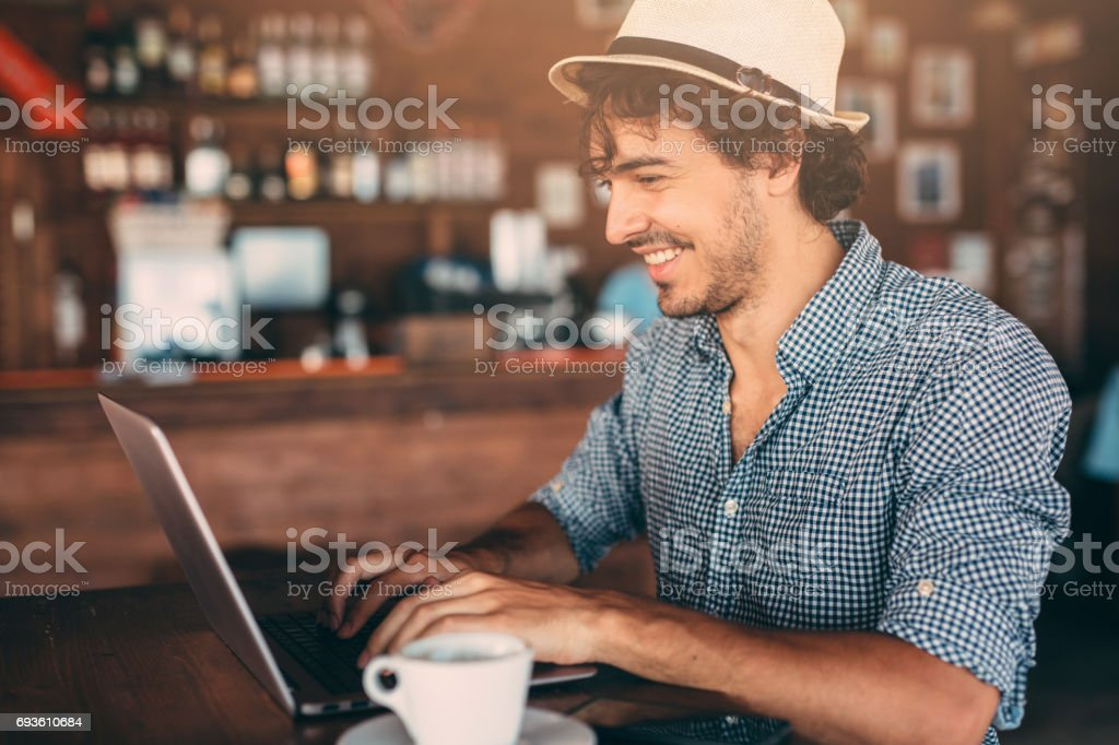 Attractive man using a laptop at the cafe royalty-free stock photo